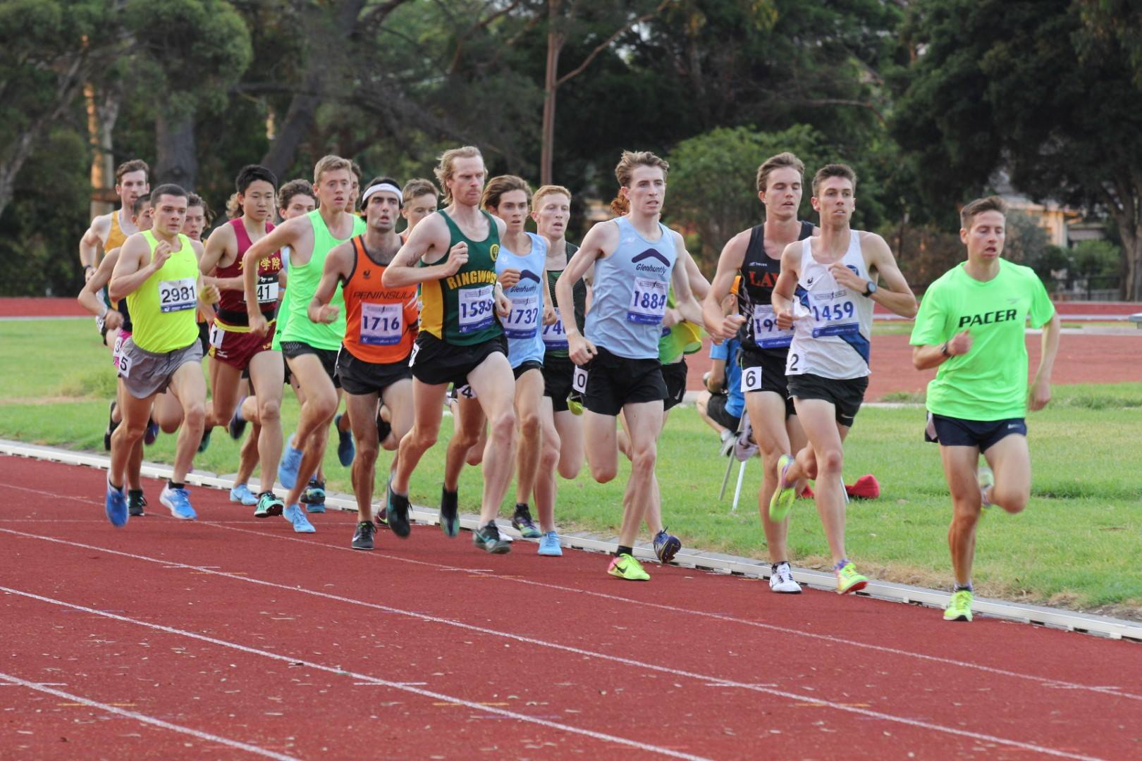 A large pack of runners bunched together on an athletics track.