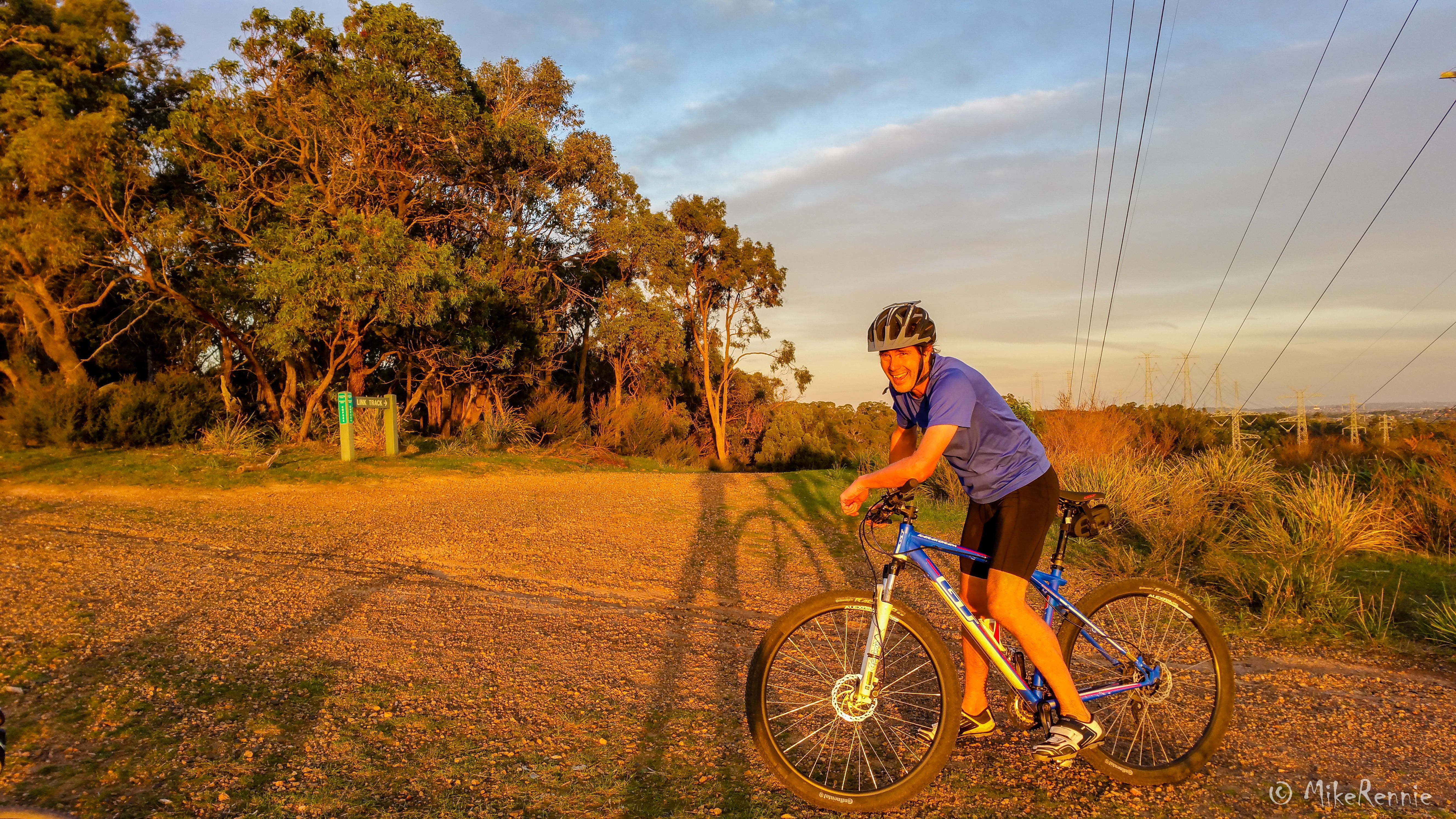 Gavin Burren resting on his bike, basked in a golden light atop a hill on North Boundary Track with 360-degree views of Melbourne. Photo taken while mountain biking at Churchill National Park during sunset by Mike Rennie on Friday 15 May 2016.