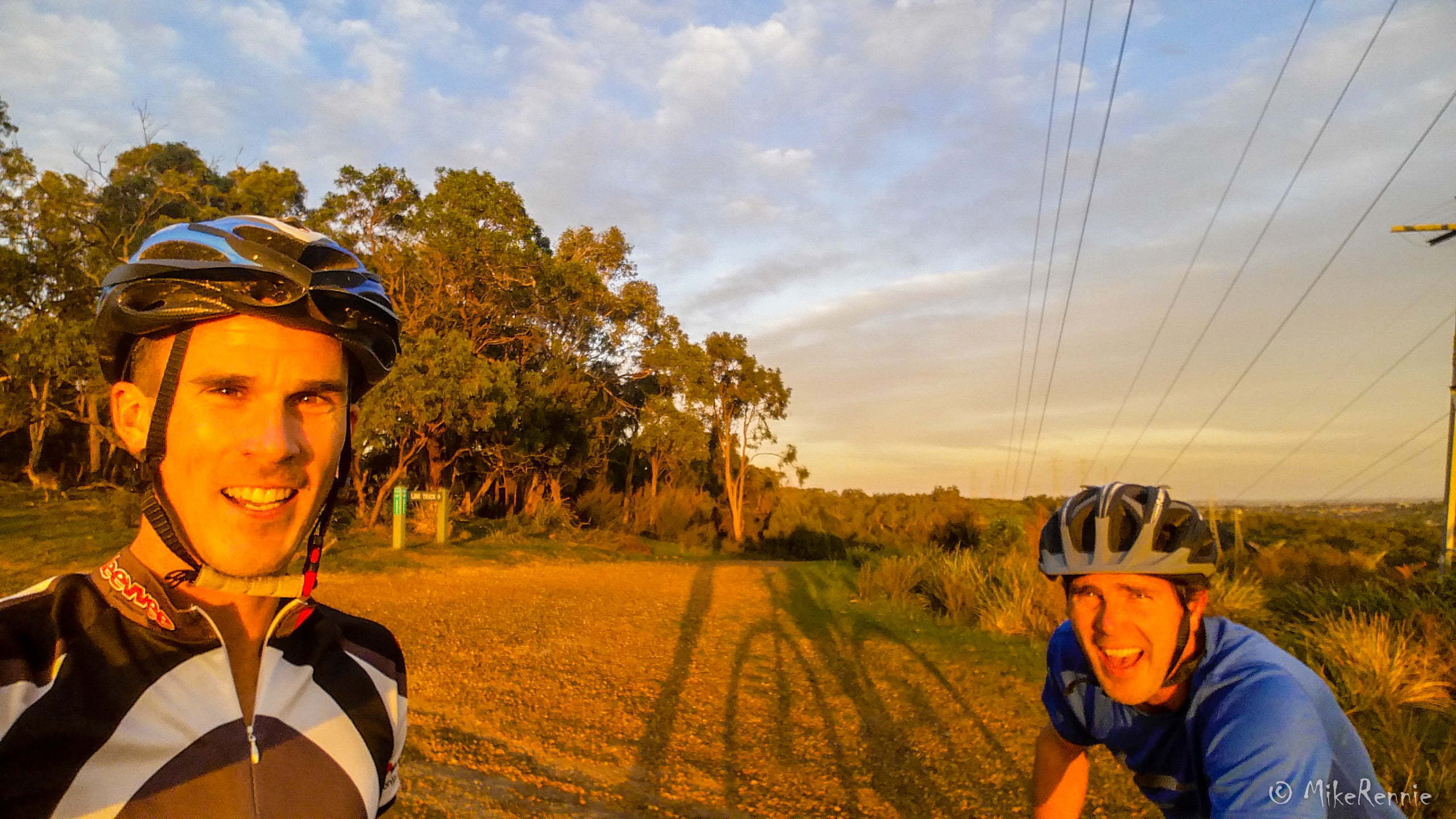Mike Rennie and Gavin Burren basking in golden light while mountain biking at Churchill National Park during sunset. Photo taken on North Boundary Track atop a hill with 360-degree views of Melbourne by Mike Rennie on Friday 15 May 2016.
